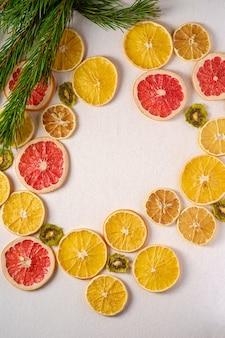 Vacaciones creativas navidad año nuevo alimentos textura de frutas con pomelo seco, kiwi, naranja y limón con rama de abeto