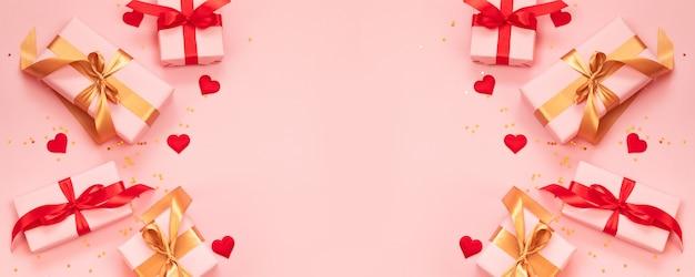 Las vacaciones del día de san valentín bordean con cajas de regalo de decoración de amor y sobre fondo rosa con espacio de copia de texto.