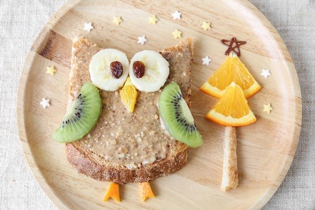 Vacaciones divertidas búho tostado con fruta, comida arte desayuno para niños