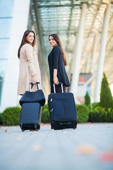 Vacaciones, dos niñas felices viajando juntas al extranjero, llevando maletas en el aeropuerto