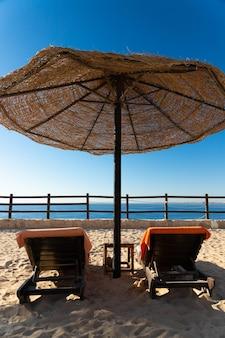 Vacaciones, dos tumbonas en la playa bajo una sombrilla en el mar rojo.