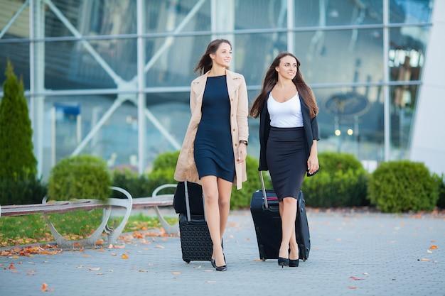Vacaciones, dos viajeros femeninas elegantes caminando con su equipaje en el aeropuerto