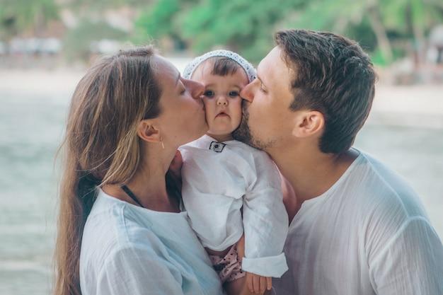 Vacaciones en familia junto al mar: hombre, mujer y niño en la playa.