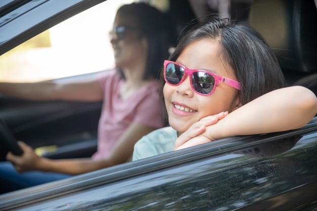Vacaciones familiares, familia feliz en un viaje por carretera en su automóvil, mamá conduciendo un automóvil mientras su hija está sentada al lado, mamá e hija están viajando. paseo de verano en automóvil.