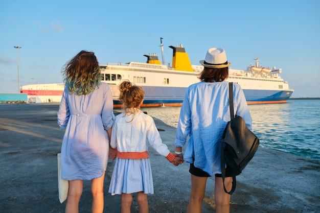 Vacaciones familiares en el mar, madre e hijas en el puerto de la mano mirando el ferry