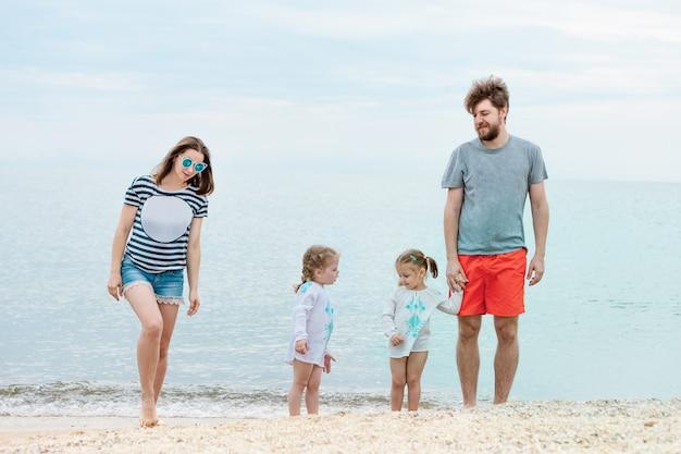 Vacaciones familiares padres e hijos en la orilla del mar día de verano