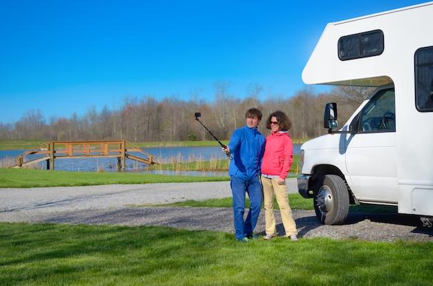Vacaciones familiares, viaje en autocaravana, pareja feliz haciendo selfie frente a la caravana en viaje de vacaciones en autocaravana