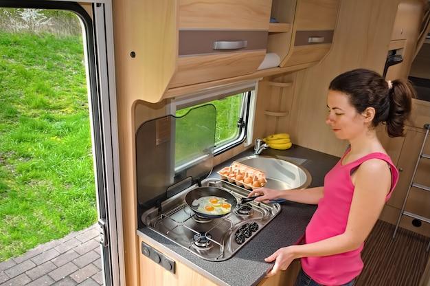 Vacaciones familiares, viaje de vacaciones rv, camping, mujer sonriente feliz cocinando en camper, interior de autocaravana