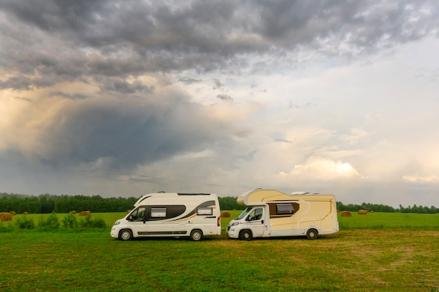 Vacaciones familiares y viajes (viaje) al aire libre en autocaravana (caravana). dos autocaravanas en un campamento de verano al aire libre. viaje (viaje) por concepto de automóvil.