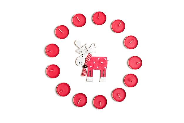 Vacaciones, invierno y concepto de celebración - composición de navidad. velas, ciervos, bac blanco