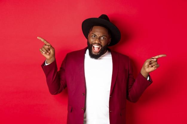 Vacaciones de invierno y concepto de compras. alegre hombre negro sonriendo y mostrando dos promo, señalando con el dedo hacia los lados en los espacios de copia, fondo rojo.