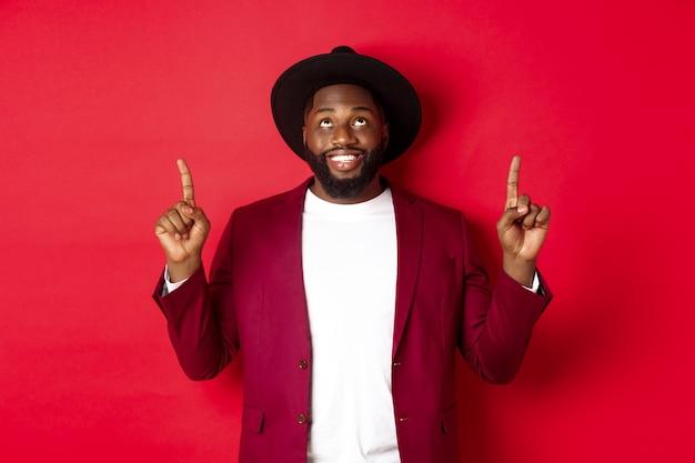 Vacaciones de invierno y concepto de compras. feliz hombre afroamericano vistiendo ropa de fiesta para año nuevo, apuntando y mirando hacia arriba con una sonrisa de satisfacción, fondo rojo.