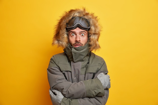 Vacaciones de invierno y concepto de deporte extremo. snowboarder conmocionado tiembla de frío se abraza a sí mismo mientras trata de calentarse durante el día helado en la estación de esquí de montaña.