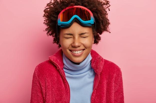 Vacaciones de invierno y concepto de vacaciones. primer plano de alegre mujer afroamericana lleva gafas de esquí, disfruta del tiempo libre, vestida con cuello alto y jersey rojo, aislado en la pared rosa.