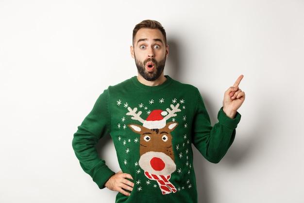 Vacaciones de invierno y navidad. hombre mirando emocionado como señalar con el dedo a la derecha en el logotipo, de pie asombrado contra el fondo blanco.