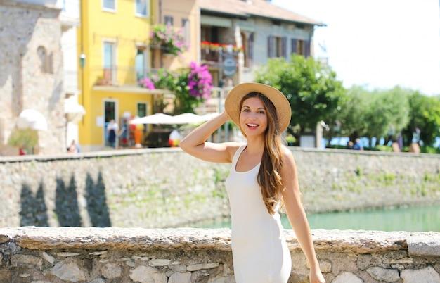 Vacaciones en italia chica turista de moda hermosa con sombrero y vestido blanco disfrutando de caminar en la ciudad de sirmione, italia.