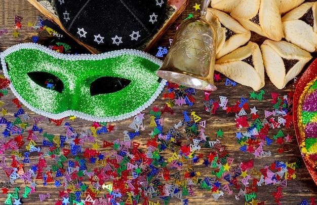 Vacaciones judías de purim con máscara de purim y purim, un objeto que hace ruido en un fondo de madera vintage con ritmo de copys