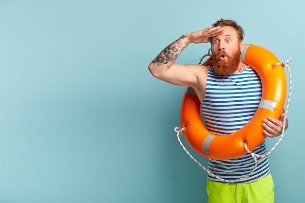 Vacaciones en el mar y concepto de resort. salvavidas estupefacto con aro salvavidas mira sorprendentemente a la distancia
