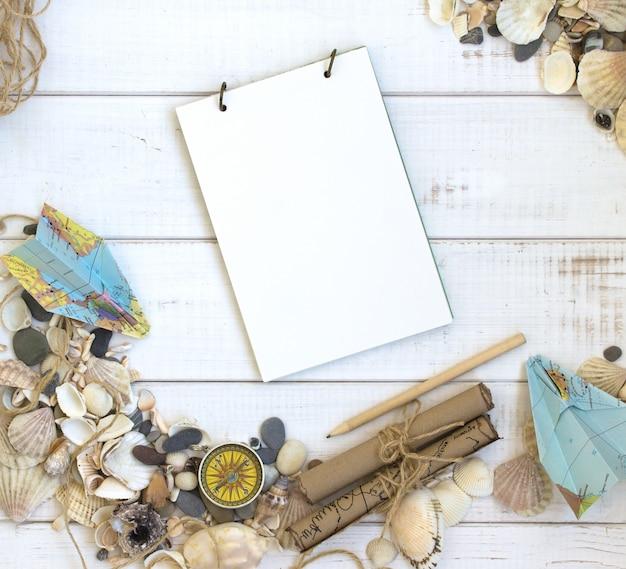 Vacaciones de mar en horario de verano, conchas marinas fondo blanco de madera, cuaderno de viaje, mapa