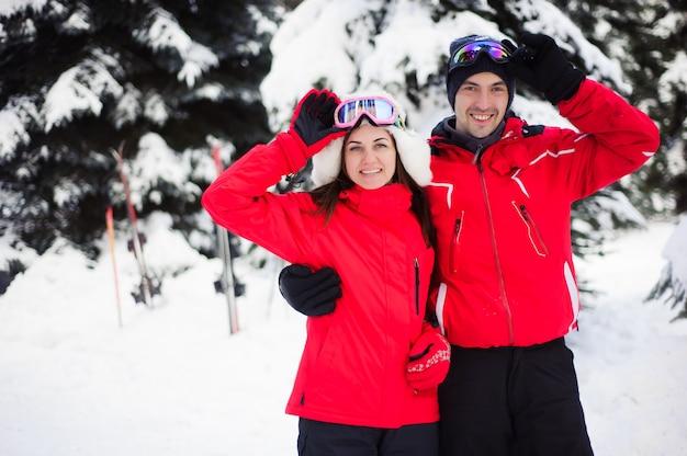 Vacaciones de navidad en el bosque de invierno. retrato de amantes con esquís disfruta del invierno en el parque.