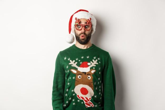 Vacaciones de navidad, concepto de celebración. chico sorprendido en gafas de fiesta y gorro de papá noel mirando hacia abajo divertido, de pie sobre fondo blanco.