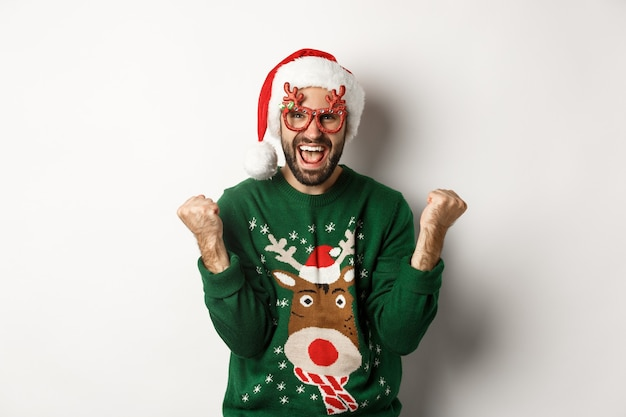 Vacaciones de navidad, concepto de celebración. hombre feliz con gorro de papá noel triunfando, vistiendo divertidas gafas de fiesta y regocijo, de pie sobre fondo blanco.