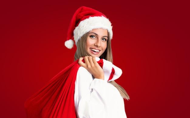 En vacaciones de navidad joven rubia recogiendo una bolsa llena de regalos sobre pared roja aislada