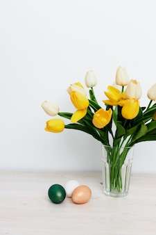 Vacaciones de pascua tulipanes amarillos en un jarrón y una habitación luminosa regala huevos tradicionales. foto de alta calidad