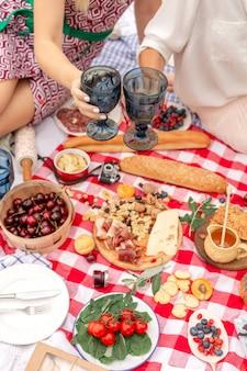 Vacaciones de picnic de verano. los amigos de la vista superior tintinean sobre una manta a cuadros
