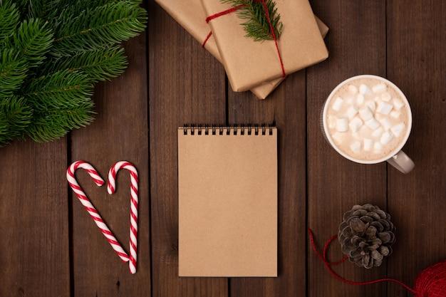 Vacaciones planas, regalos envueltos con papel artesanal, cuaderno con papel en blanco y abeto en una mesa rústica de madera oscura