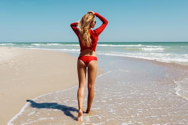 Vacaciones en la playa. hermosa mujer caliente en bikini rojo de pie con los brazos levantados a la cabeza