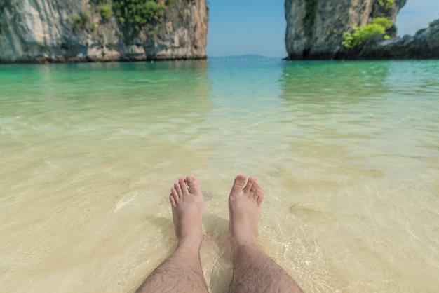Vacaciones en la playa de verano del océano, los pies en la arena de mar con olas de burbujas flotan.