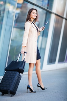 Vacaciones. sonriente pasajera procediendo a la puerta de salida tirando de la maleta a través del vestíbulo del aeropuerto