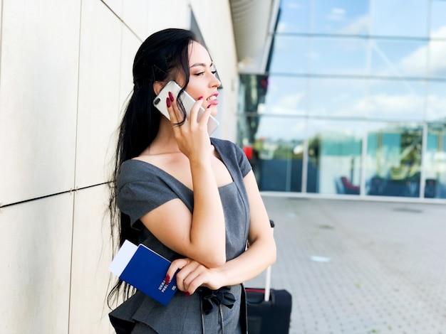 Vacaciones. sonriente pasajera que procede a la puerta de salida tirando de la maleta a través de la explanada del aeropuerto