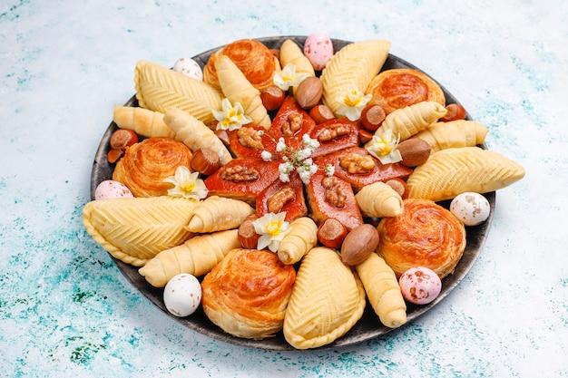 Vacaciones tradicionales de azerbaiyán novruz cookies baklavas y shakarburas en bandeja negra sobre la mesa
