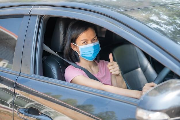 Vacaciones de vacaciones, coronavirus covid-19 y mascarilla, mujer con mascarilla conduciendo su automóvil durante la pandemia de coronavirus, nueva normalidad para mantenerse a salvo, viaje de verano en automóvil.