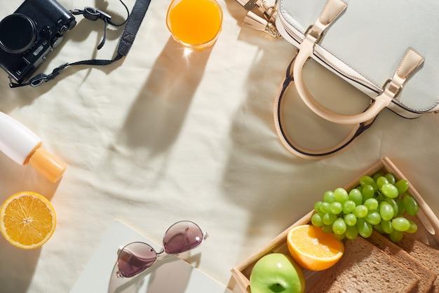 Vacaciones de verano con bolsa, fruta, crema solar, gafas, accesorios sobre fondo blanco.