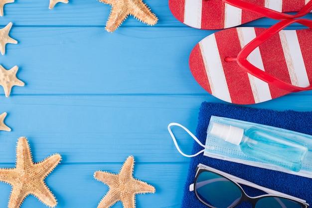 Vacaciones de verano y concepto de cuarentena. arriba, arriba, vista aérea, primer plano, foto, de, toalla, gafas de sol, estrella de mar, desinfectante, máscara, y, flipflops, aislado, en, azul, fondo de madera, con, copyspace