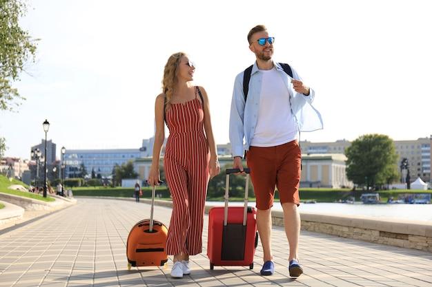 Vacaciones de verano, concepto de turismo - pareja sonriente con equipaje.