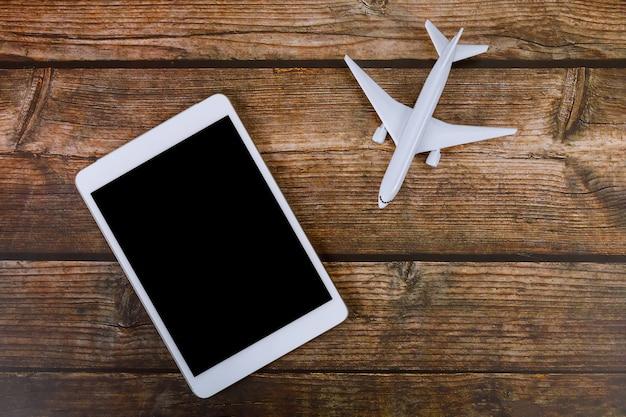 Vacaciones de verano en concepto de viaje de fondo de mesa de madera con uso de tableta digital en avión modelo de avión
