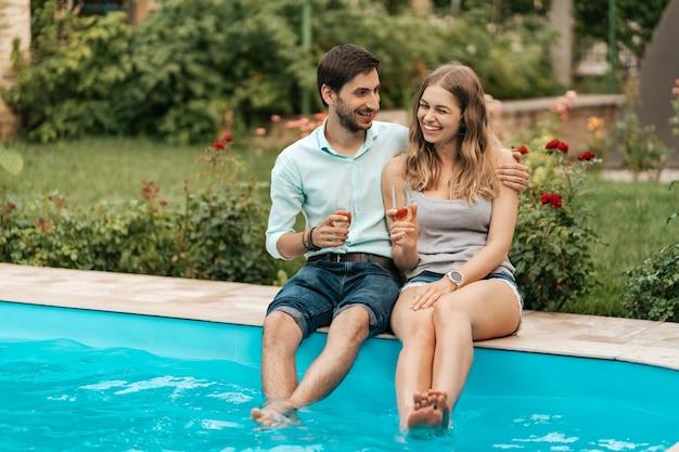 Vacaciones de verano, gente, romance, concepto de citas, pareja bebiendo vino espumoso mientras disfruta del tiempo juntos sentados en la piscina