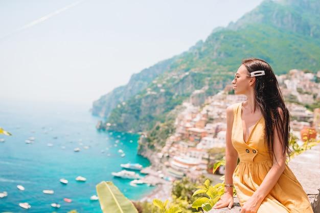 Vacaciones de verano en italia. mujer joven en el pueblo de positano en el fondo, costa de amalfi, italia
