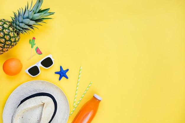 Vacaciones de verano sombrero de paja, gafas de sol blancas, frutas tropicales, jugo fresco y accesorios de cóctel sobre amarillo