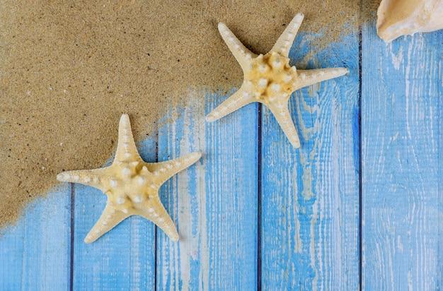 Vacaciones de verano en tablas de madera azules con estrellas de mar en la arena de la playa