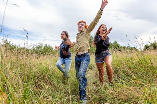Vacaciones de verano vacaciones concepto de gente feliz. grupo de tres amigos niño y dos niñas corriendo y divirtiéndose juntos al aire libre.