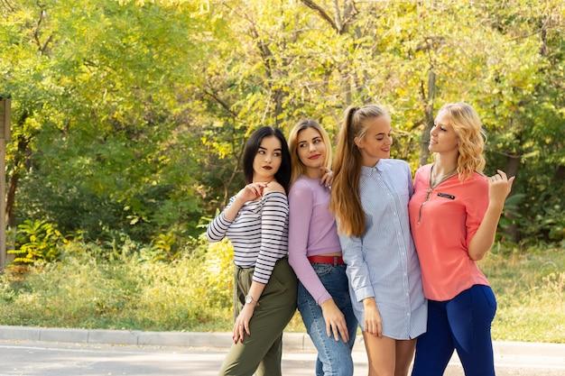 Vacaciones de verano, vacaciones, viajes y concepto de personas - grupo de mujeres jóvenes en el parque