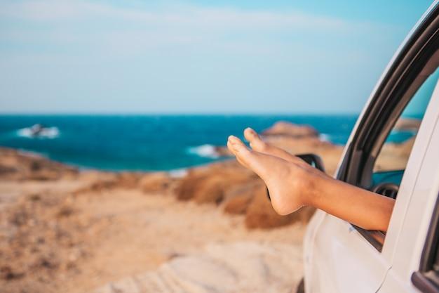 Vacaciones de verano, vacaciones, viajes, viaje por carretera y concepto de personas: cerca de los pies que se muestran desde la ventana del automóvil