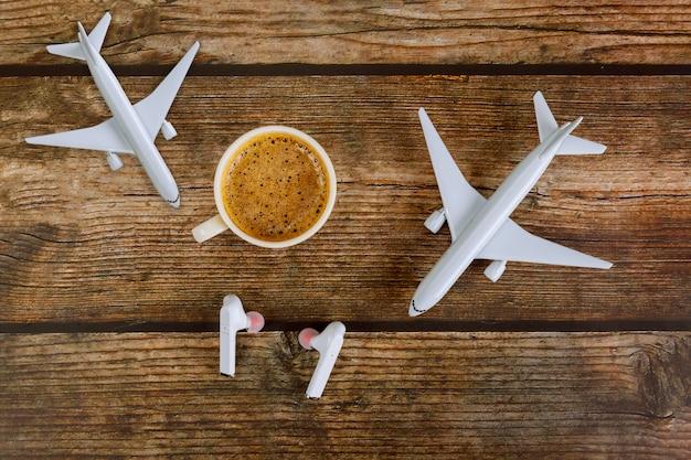 Vacaciones de verano viajando concepto de planificación avión modelo avión y auriculares en taza de café
