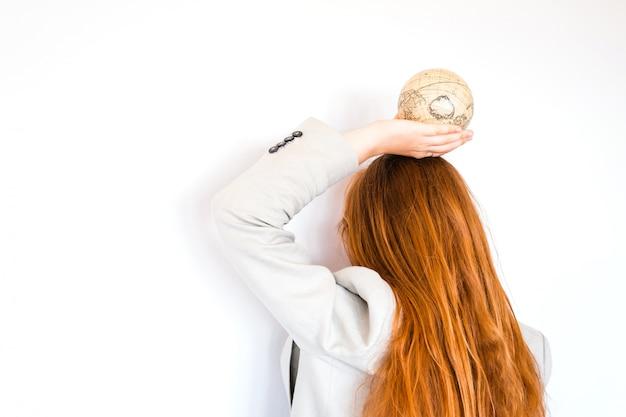 Vacaciones viajes verano fin de semana aventura concepto de viaje. muchacha roja del pelo que sostiene el globo antiguo de la vendimia aislado en el fondo blanco. copia espacio maqueta para agencia de turismo. idea de educación y descubrimiento