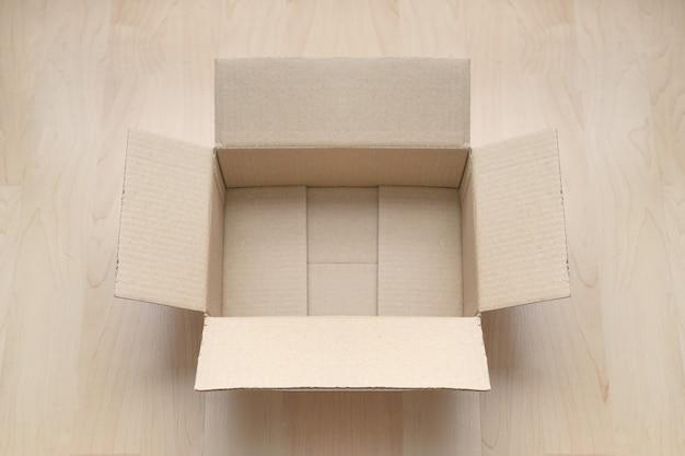 Vaciar caja de cartón rectangular abierta sobre madera.